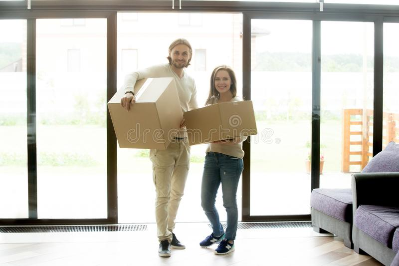 Portrait of happy couple carrying boxes moving into new house stock photos