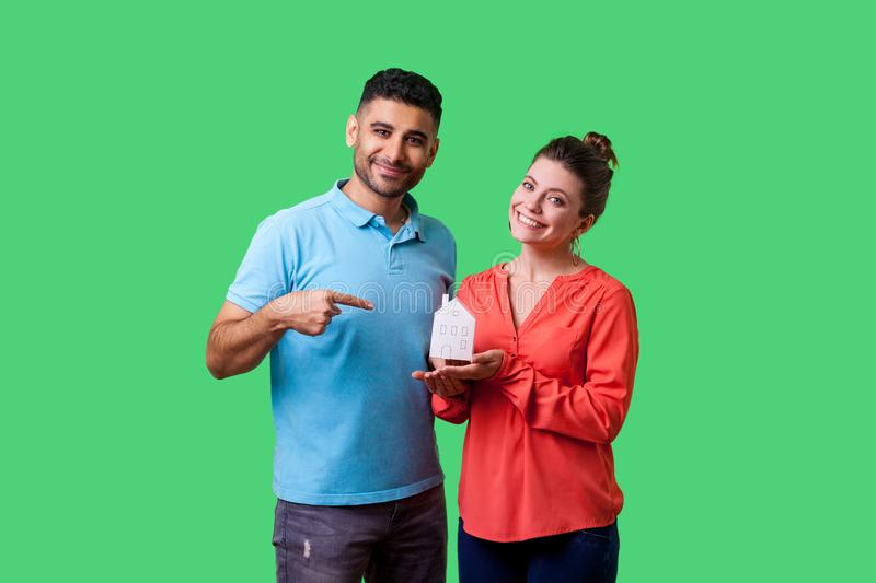 Portrait of happy couple in casual clothes dreaming of own home. isolated on green background, indoor studio shot stock images