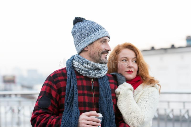 Portrait of happy couple with coffee cup. Couple has date on city street. Loving couple looking to right way. stock photography