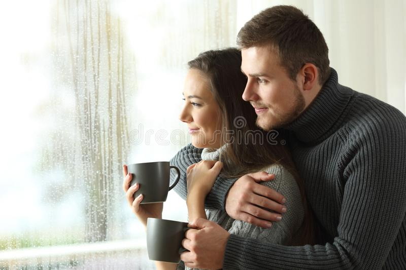 Couple looking through a window in a rainy day royalty free stock photos