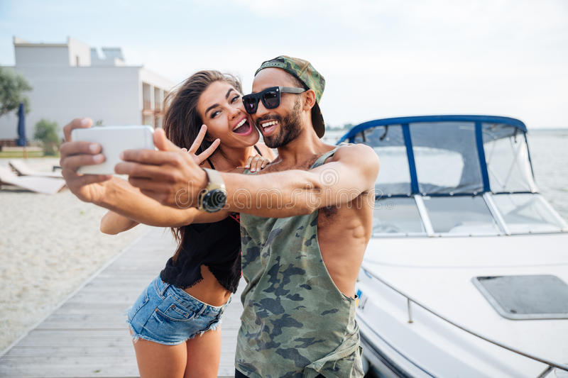 Portrait of a happy couple making selfie photo on smartphone stock photography