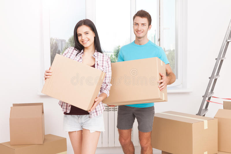 Portrait of happy couple in new home. Young couple holding a box and smiling happily at the camera royalty free stock images