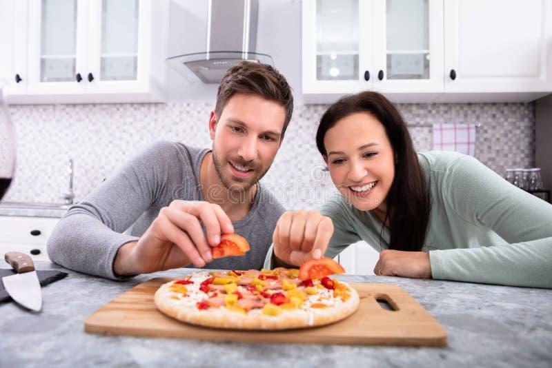 Happy Couple Preparing Pizza. Portrait Of Happy Couple Preparing Pizza In Kitchen royalty free stock photo