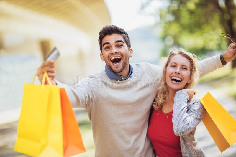 Portrait of happy couple with shopping bags after shopping in ci stock photography