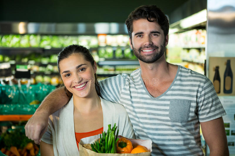 Portrait of happy couple standing with a grocery bag in organic section. Of supermarket stock photography