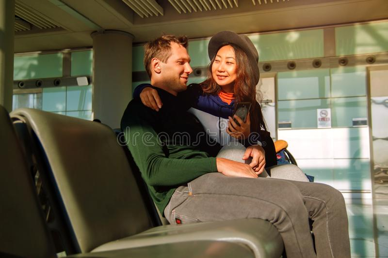 Portrait of happy couple using mobile phone at airport. Handsome young men and beautiful asian women  using mobile phone at airport near window, waiting for royalty free stock image