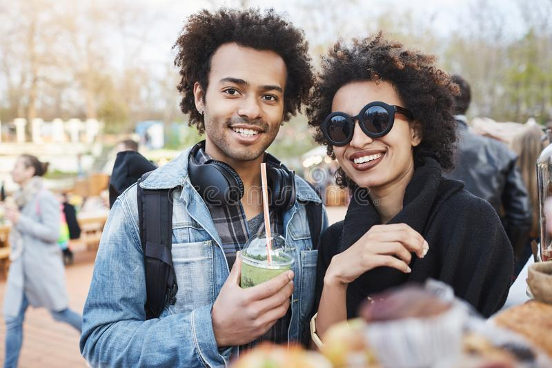 Portrait of happy cute dark-skinned couple with afro hairstyle, strolling on food festival, tasting and drinking stock image