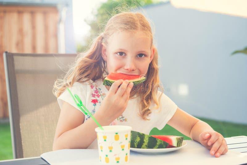 Portrait of happy cute little girl eating sweet red watermelonin garden stock photo