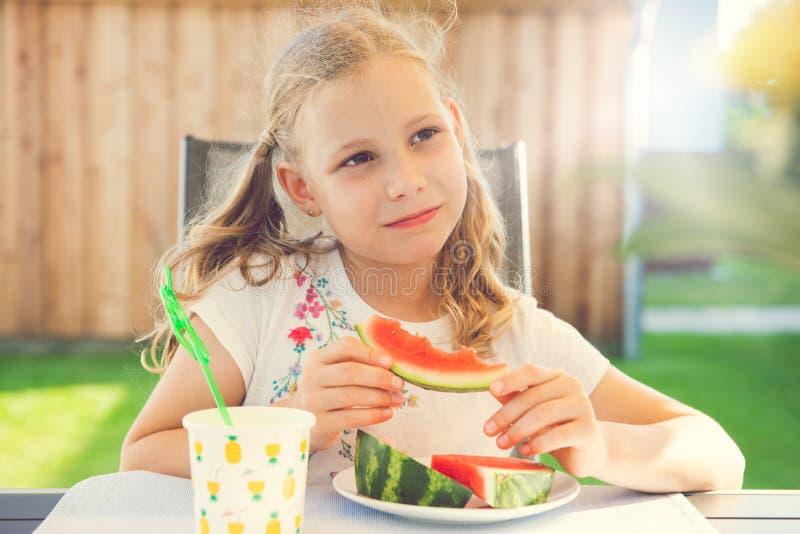 Portrait of happy cute little girl eating sweet red watermelonin garden stock photos