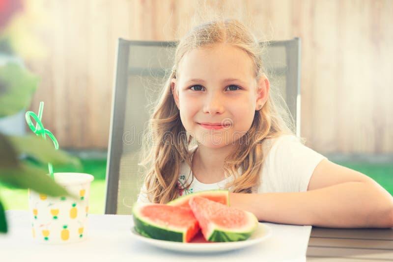 Portrait of happy cute little girl eating sweet red watermelonin garden stock photography