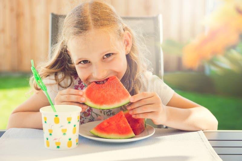Portrait of happy cute little girl eating sweet red watermelonin garden royalty free stock photo