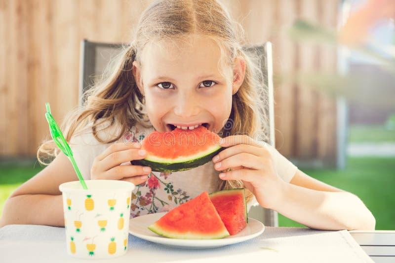 Portrait of happy cute little girl eating sweet red watermelonin garden stock image