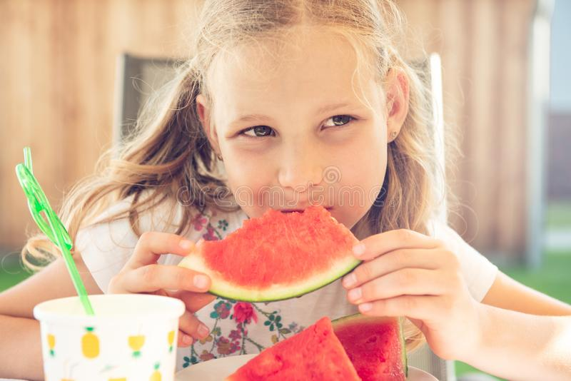 Portrait of happy cute little girl eating sweet red watermelonin garden royalty free stock images