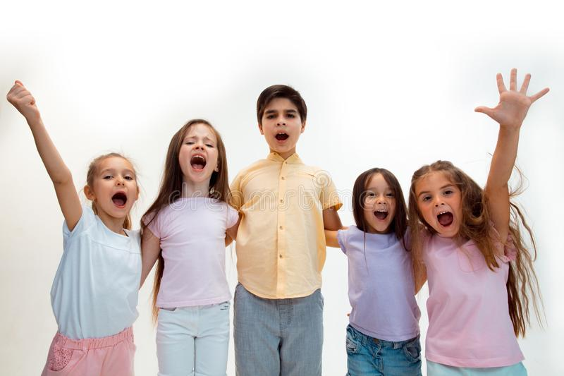 The portrait of cute little boys and girls in stylish clothes looking at camera at studio stock photo