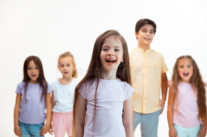 The portrait of cute little boys and girls in stylish clothes looking at camera at studio stock photography