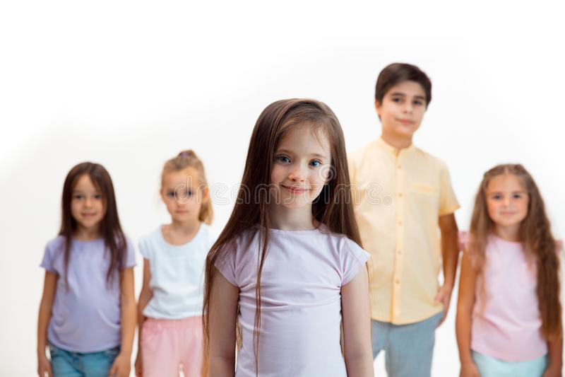 The portrait of cute little boys and girls in stylish clothes looking at camera at studio stock image
