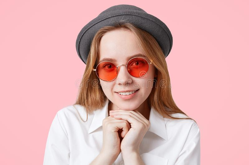 Portrait of happy delighted female model in round red sunglasses and elegant hat, keeps hands under chin, smiles broadly, isolated stock photography