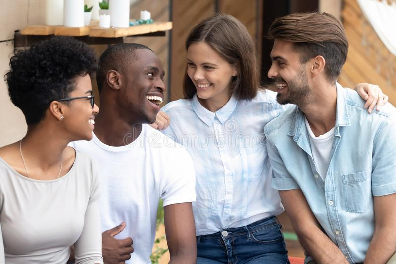 Portrait of happy diverse millennial friends hug at meeting stock photo
