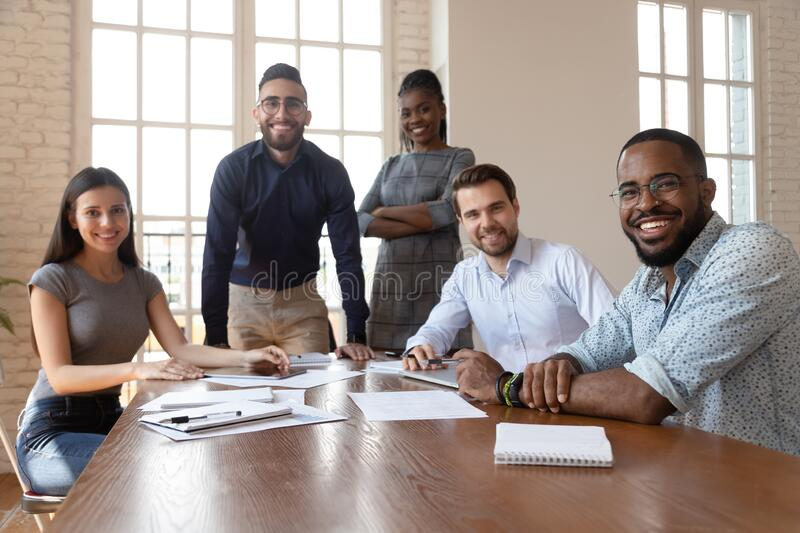 Multiethnic smiling employees gather at boardroom meeting royalty free stock photos