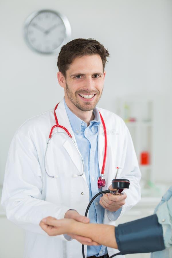 Portrait happy doctor checking patients blood pressure in clinic. Portrait of happy doctor checking patients blood pressure in clinic stock photos