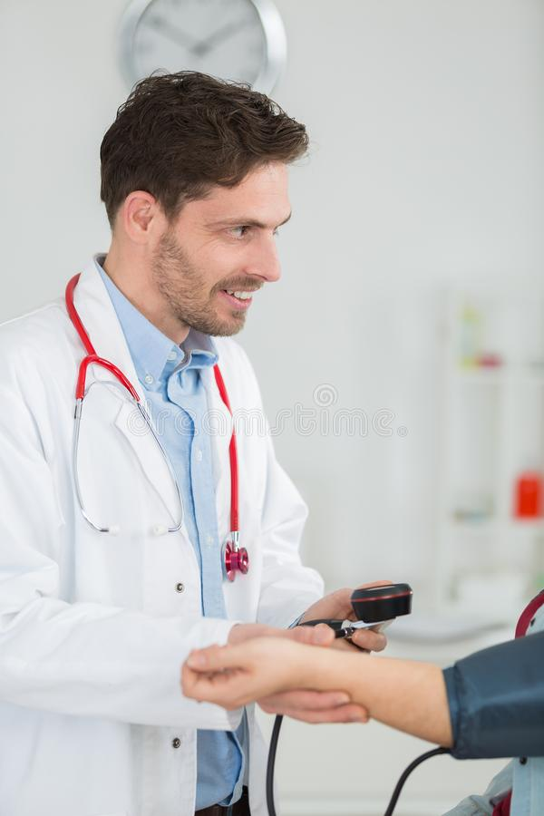 Portrait happy doctor checking patients blood pressure in clinic. Portrait of happy doctor checking patients blood pressure in clinic royalty free stock images