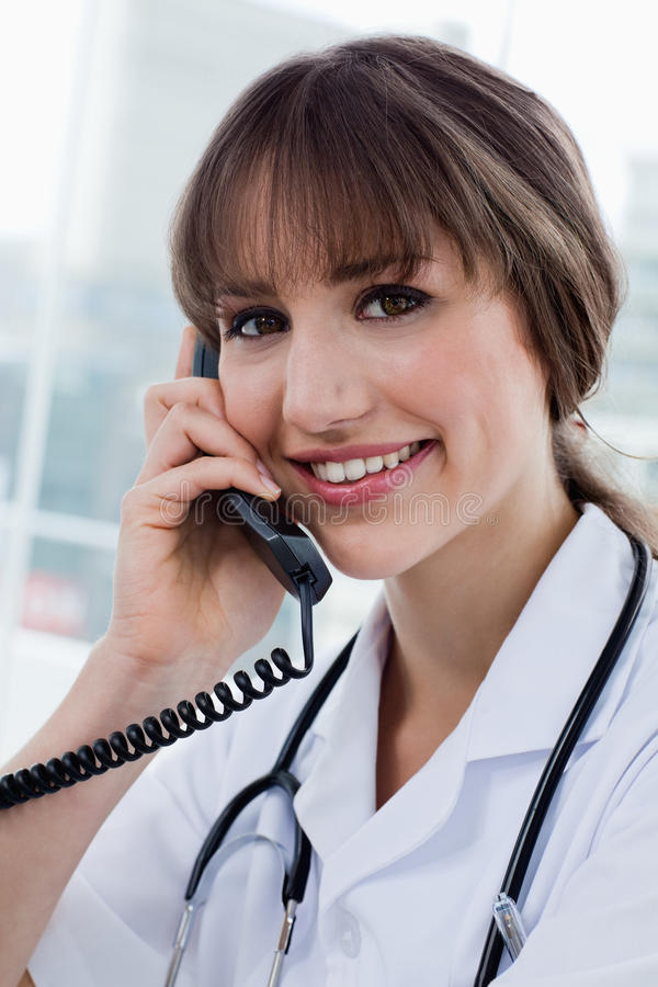Portrait of a happy doctor on the phone. In her office stock image