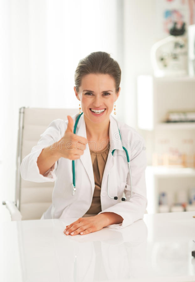 Portrait of happy doctor woman showing thumbs up stock images