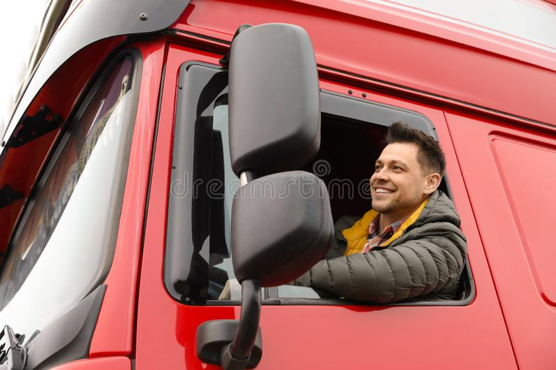 Portrait of happy driver in cab of truck. Portrait of happy driver in cab of modern truck royalty free stock images