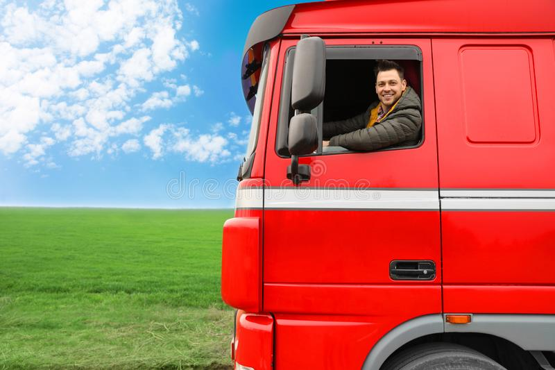 Portrait of happy driver in cab of truck. Portrait of happy driver in cab of modern truck stock photos