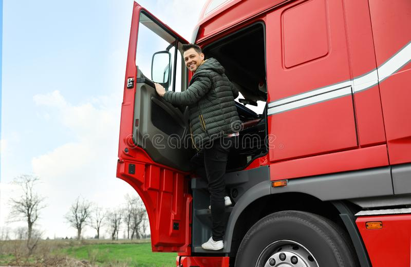 Portrait of happy driver getting into cab of truck. Portrait of happy driver getting into cab of modern truck royalty free stock images