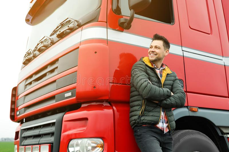 Portrait of happy driver at modern truck. Outdoors stock photo