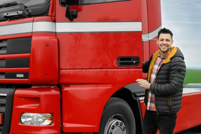 Portrait of happy driver opening door of modern truck. Outdoors stock photography