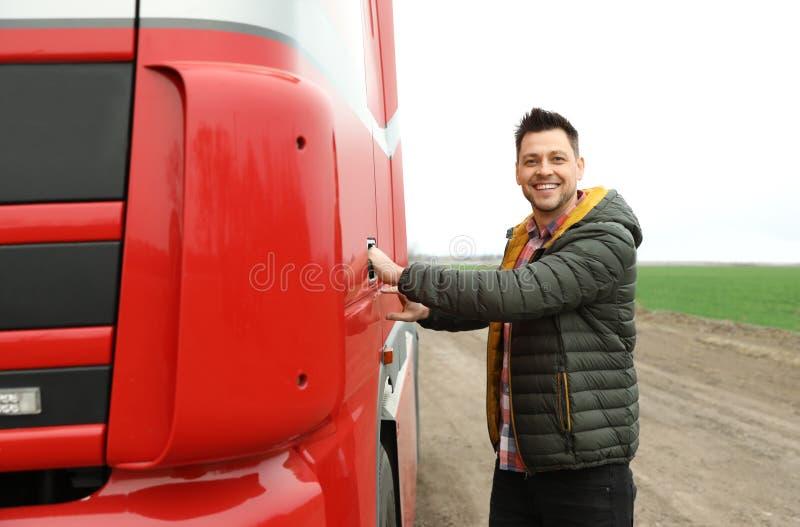 Portrait of happy driver opening door of modern truck. Outdoors stock images