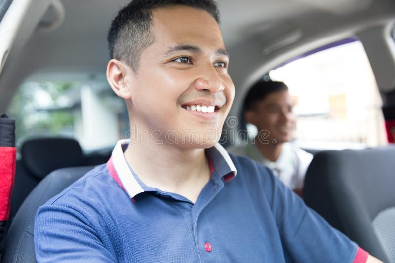 Happy driver taking his customer. Portrait of happy driver taking his customer by car stock image