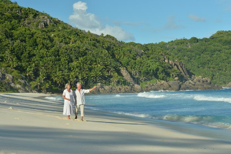 Portrait of happy elderly couple walking on tropical beach royalty free stock images