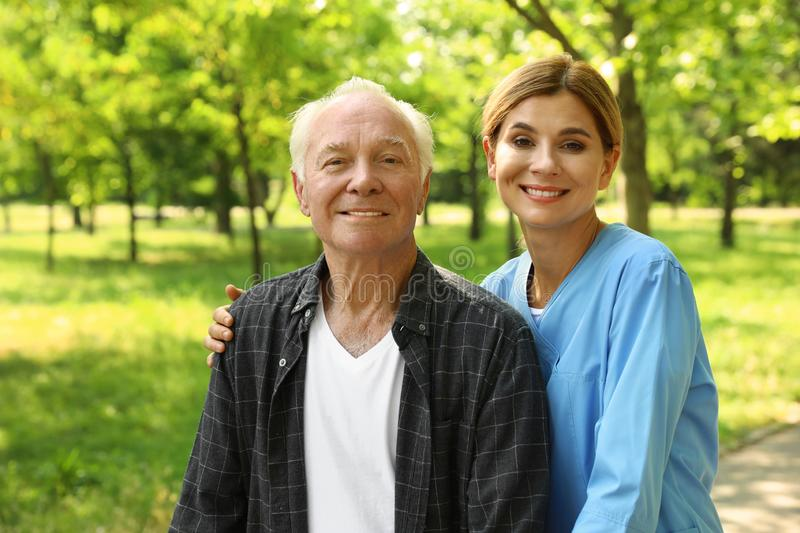 Portrait of happy elderly man and nurse in sunny park royalty free stock photography