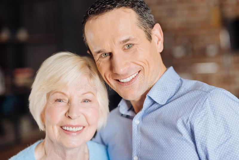 Portrait of happy elderly woman and her handsome young son royalty free stock photography