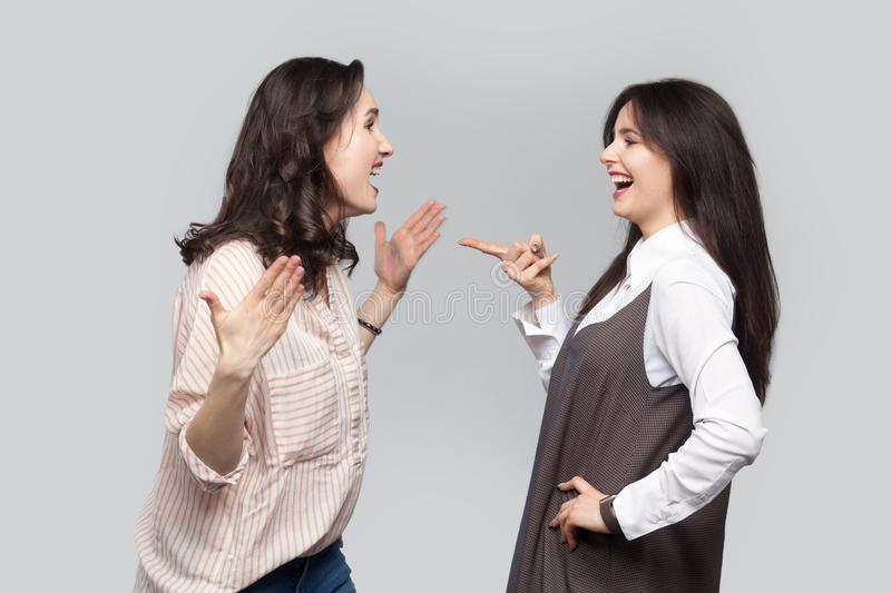 Portrait of happy emotional beautiful best friends in casual style standing talking, discussing together. she pointing and telling stock photo
