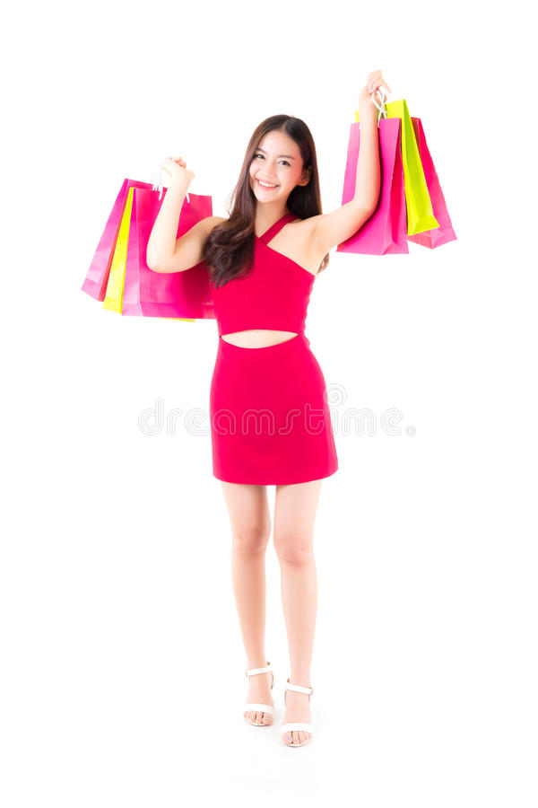 portrait of a happy excited asian woman in red dress standing and holding color paper bag. stock photos