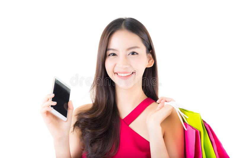 Portrait of a happy excited asian woman in red dress standing talking phone. And holding colorful shopping bags with happy isolated on a white background stock photo