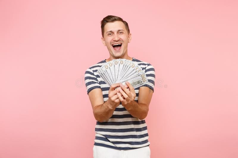 Portrait of happy excited young man in striped t-shirt holding bundle lots of dollars, cash money, ardor gesture on copy. Portrait of smiling excited young man stock photo