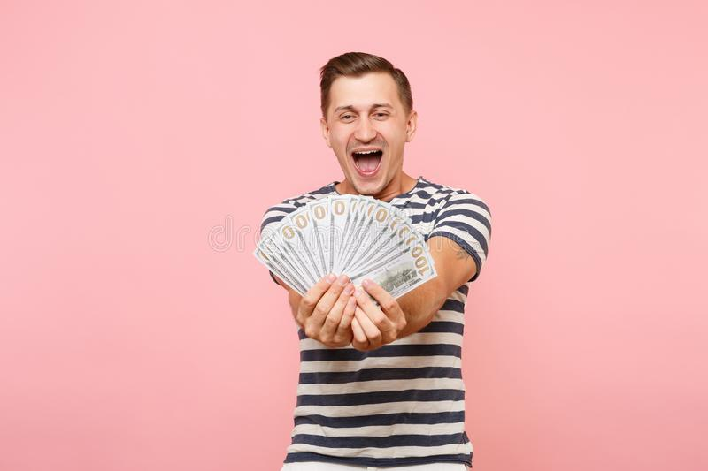 Portrait of happy excited young man in striped t-shirt holding bundle lots of dollars, cash money, ardor gesture on copy. Portrait of smiling excited young man royalty free stock images