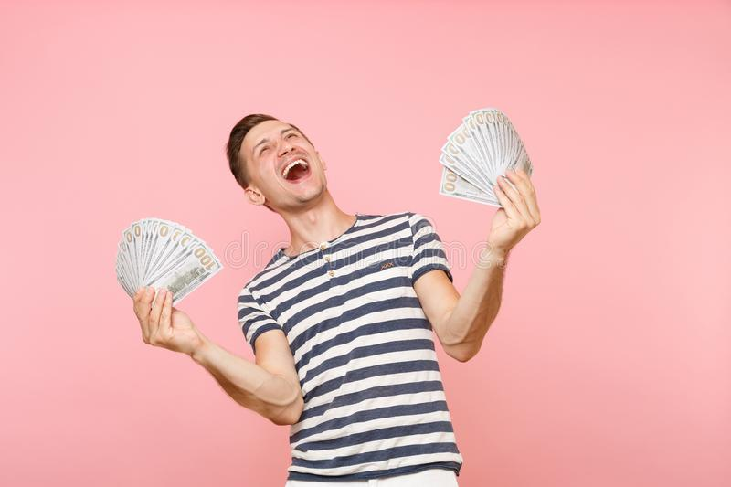 Portrait of happy excited young man in striped t-shirt holding bundle lots of dollars, cash money, ardor gesture on copy. Portrait of smiling excited young man royalty free stock image