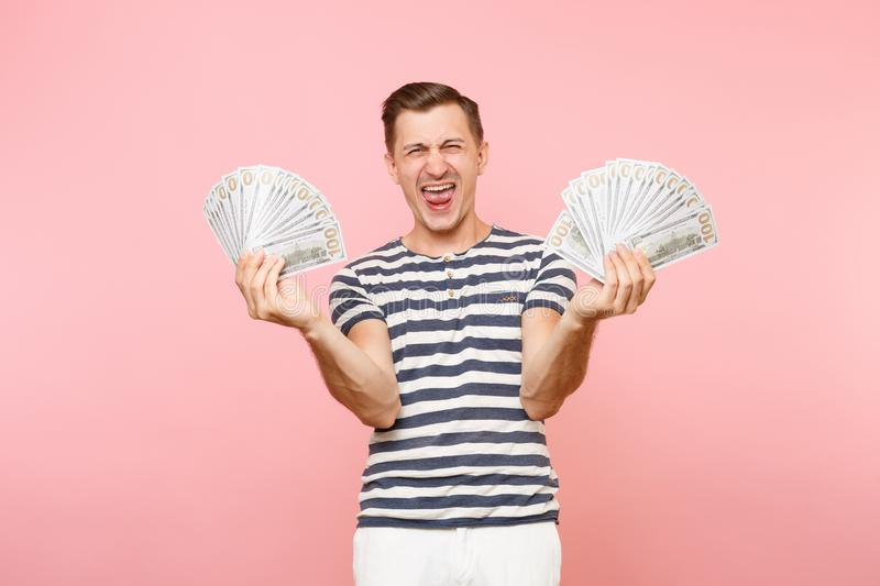 Portrait of happy excited young man in striped t-shirt holding bundle lots of dollars, cash money, ardor gesture on copy. Portrait of smiling excited young man stock images