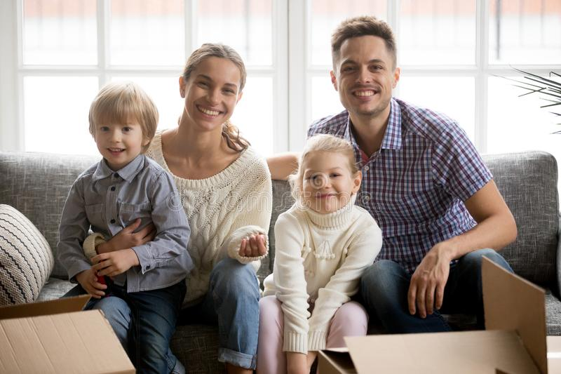 Portrait of happy family with adopted children on moving day stock images