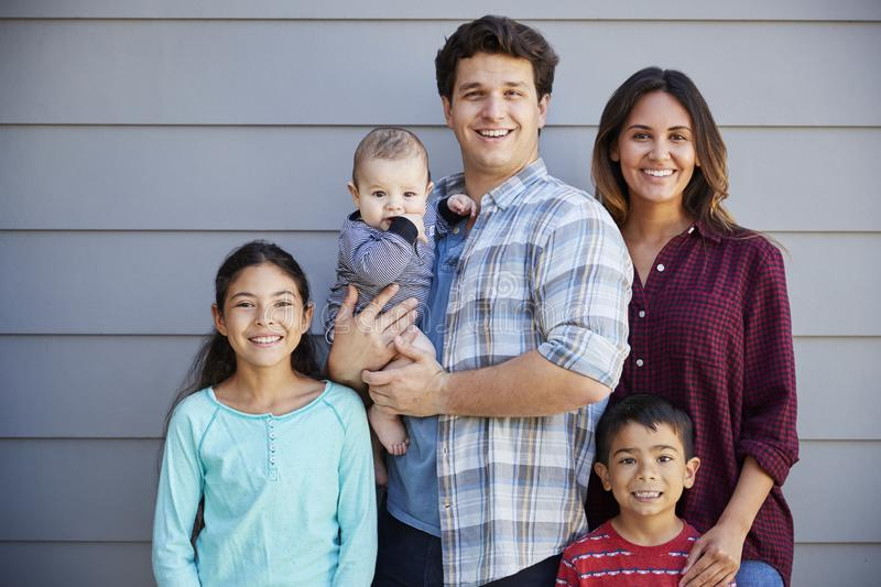 Portrait Of Happy Family With Baby Standing Outside Grey Clapboard House stock images