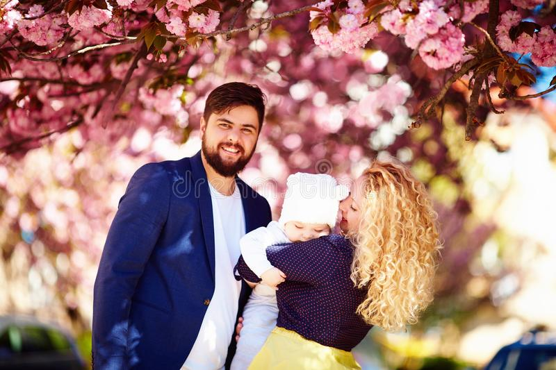 Portrait of happy family in blooming spring park stock photo