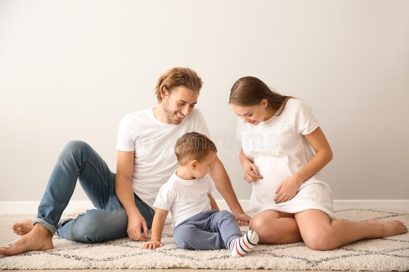 Portrait of happy family on carpet near white wall stock images