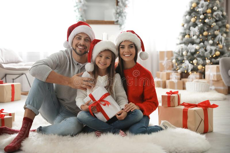 Portrait of happy family with Christmas gifts on floor stock image