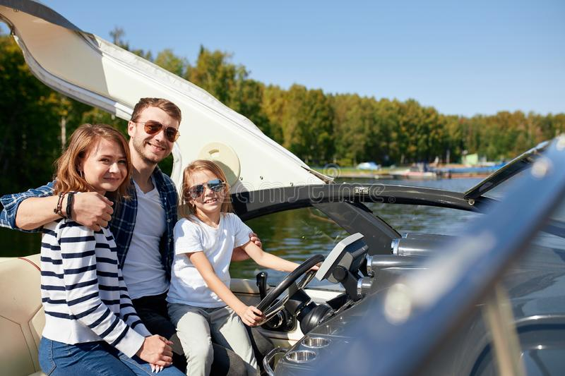 Happy family with daughter on sailing boat at sunny autumn day royalty free stock photography
